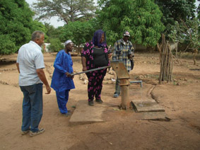 Judy Browne (centre) at the water pump in a village in Gambia